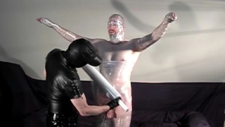Man being mummified in clear wrap