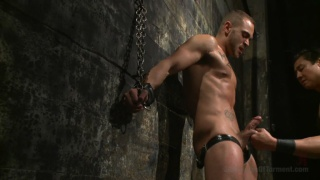 bound stud chained to a wall screams in pain