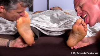 2 men lick sleeping hunk's feet