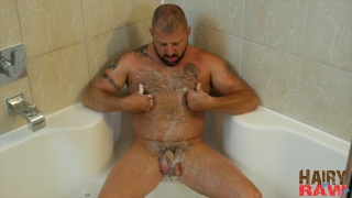 hairy man sits on shower floor and jacks off