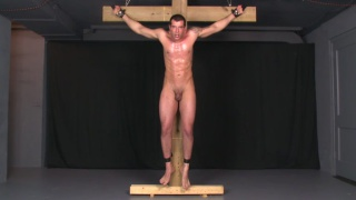 muscle hunk roped to a cross