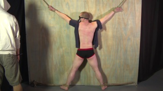 blond sub tied to a wall and caned