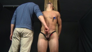 latin boy roped to a wooden post