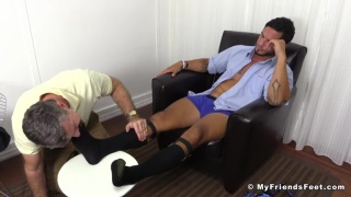 handsome executive gets his socked feet worshipped