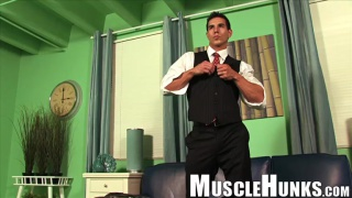 muscle hunk strips at his desk in office