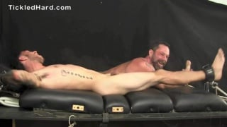 young businessman strapped down and tickled