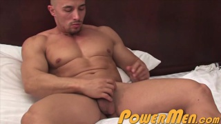 bald muscle hunk sits back in bed and strokes