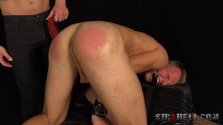 blond guy shackled, gagged and spanked