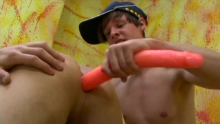 horny twink gets a long orange dildo up his ass