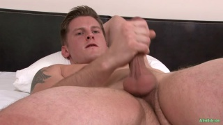 handsome hunk jerks his dick in bed
