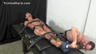 damian is strapped tightly to the tickling table