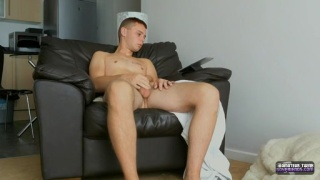 blond lad holds his nuts and strokes his cock