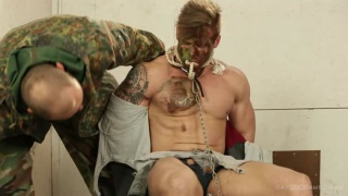 beefy soldier ties his captive to a chair