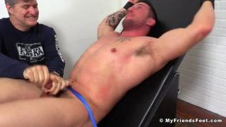 tall hunk strapped into the tickling chair
