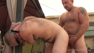 beefy daddy bends over his bottom outside