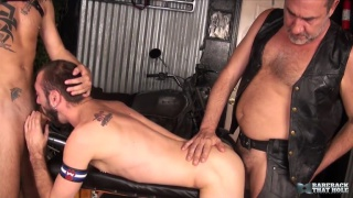 two leather men share bottom's ass