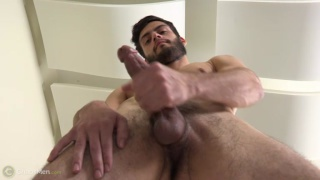 bearded guy ansel plays with his cock
