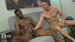white guy reaches across & grabs black guy's cock