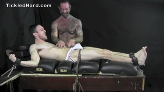 bearded guy in jockstrap strapped to tickling table