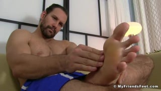 bearded stud rubs his big bare feet