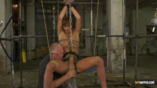 slave boy in leather harness strung up by chains