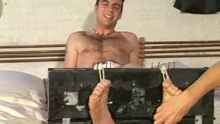 furry guy restrained in foot stockades for tickling session