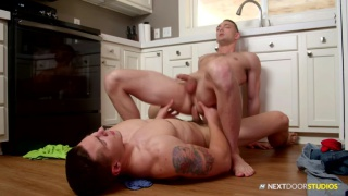 guy lies on kitchen floor while buddy rides his dick