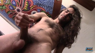 long-haired hipster strokes his uncut cock