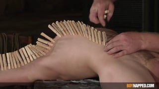 master pulls the pegs away from slave boy's welting skin