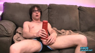 bespectacled guy pumps his big dick with red sex toy