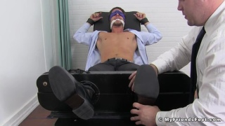 executive in suit tied up in tickling chair