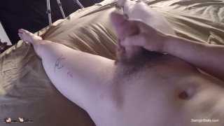 guy wearing a cowboy hat jerks off on his bed