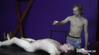 guy in jeans drips hot wax on naked guy's sensitive body