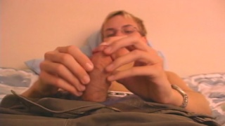 bespectacled blond lad strokes his uncut cock