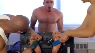 two guys tickle this dude's restrained bare feet