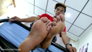 asian boy rubs his stiff cock on the soles of his feet