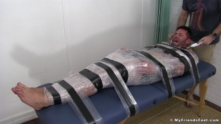 Muscle Man Mummified in Plastic for Tickling Session