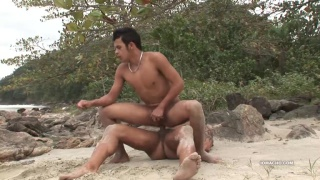 latino guy rides his buddy's cock on the beach