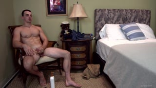 sexy guy sits in comfy chair by his bed jerking off