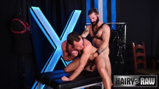 bearded man in leather harness fucking his buddy
