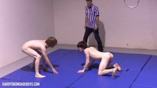 master referees as two slave boys wrestle naked