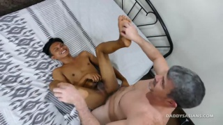 daddy holds his asian boy's tiny feet and screws him