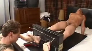guy's feet restrained in stocks while he gets tickled
