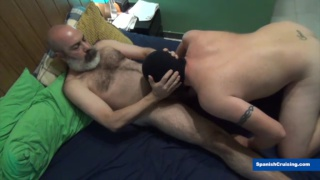 daddy with a grey beard enjoys a blowjob from a masked man