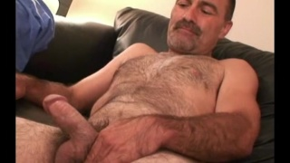ruggedly handsome hairy man strokes his dick