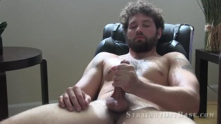 bearded guy with curly hair jerks his cock