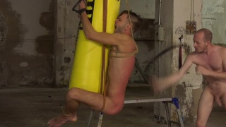 guy tied to a punching bag and beaten