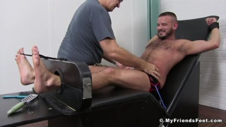 bearded guy strapped into the tickling chair