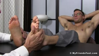 bespectacled stud enjoys foot worshipping with hands behind his head