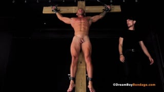 young bodybuilder strung up on a wooden cross